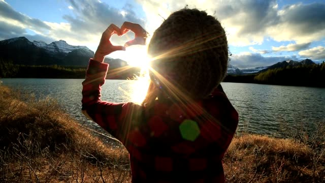 Young woman making heart shape frame with hands to sunset video