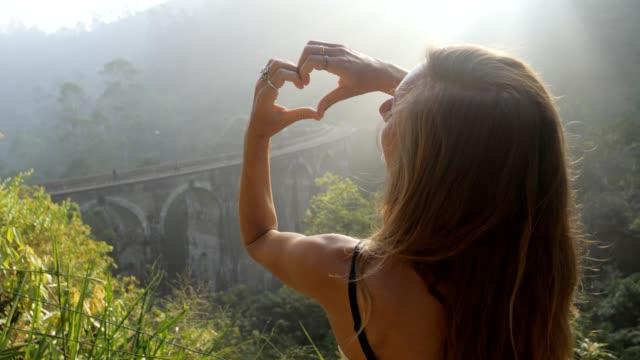 stockvideo's en b-roll-footage met jonge vrouw die hartvorm met handen op mooi landschap van de theeplantage en oude boogbrug in sri lanka het houden van reis en het onderzoeken van land maakt. het hart van de meisjeliefde bij zonsondergang op beroemde plaats - camelia white