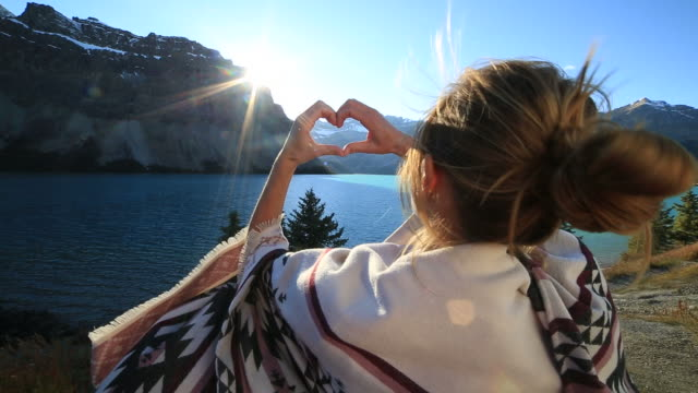 Young woman making heart to spectacular lake mountain scenery video