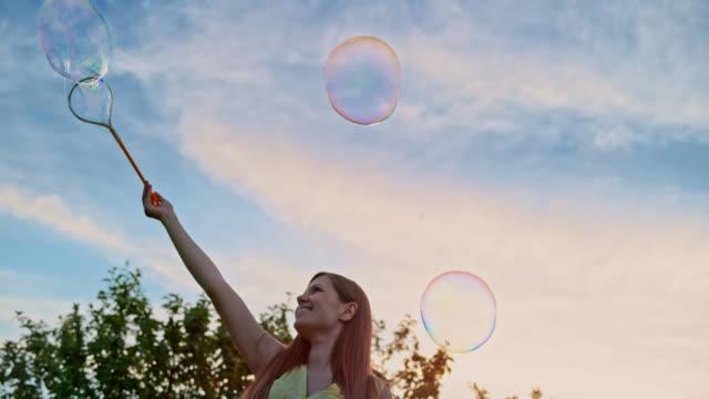 vidéos et rushes de slo mo jeune femme faire de grosses bulles de savon et souriant - charmeur