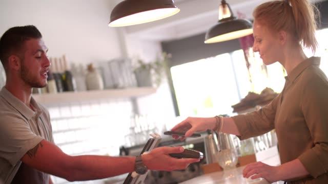 vídeos de stock, filmes e b-roll de jovem mulher fazendo nfc smartphone pagamento sem contato no café - pagando