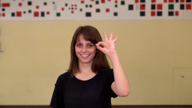 young woman making ok sign over wall background indoors. - znak ok filmów i materiałów b-roll