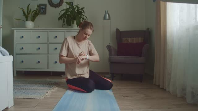 自宅で板運動をする若い女性 - スポーツ用品点の映像素材/bロール