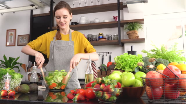 young woman making salad in the kitchen - vegan stock videos and b-roll footage