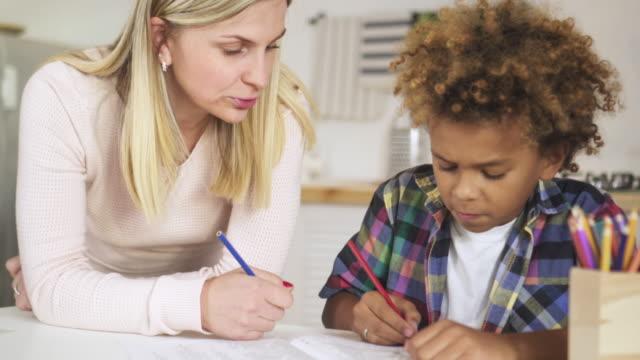 młoda kobieta mama pomaga swojemu synowi przygotować szkolną pracę domową - jeden rodzic filmów i materiałów b-roll