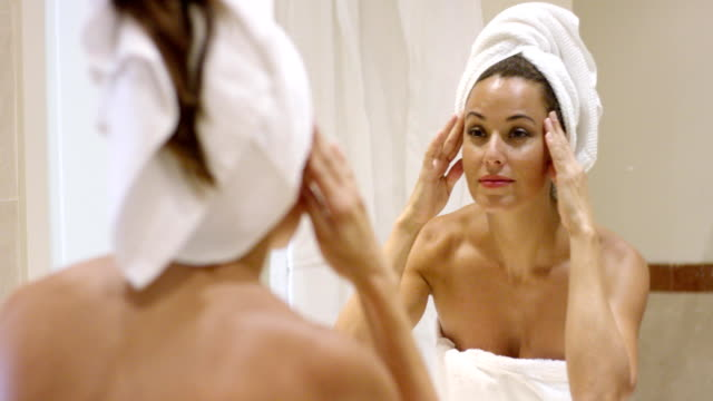 Young woman massaging her temples Young woman massaging her temples with her fingertips as she stands in front of a mirror in a bathroom wrapped in a white towel wearing a towel stock videos & royalty-free footage