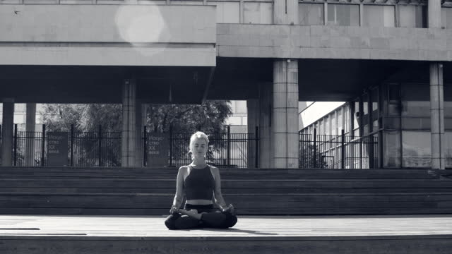 Young woman meditating against modern building Young woman meditating outdoors against modern building at summer day russian ethnicity stock videos & royalty-free footage