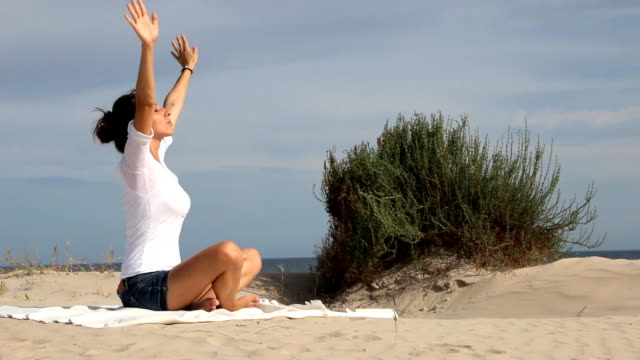 Young woman meditating near the sea video