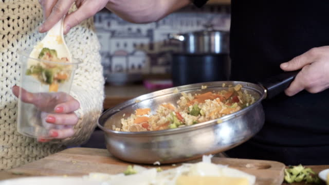 young woman mixing vegetables on pan, dolly shot video