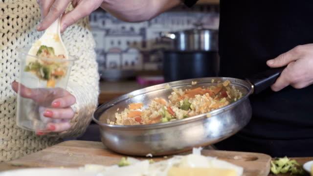 jeune femme, mélange de légumes sur pan, coup de dolly - Vidéo