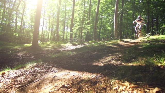 Young woman mountain biking through a forest video