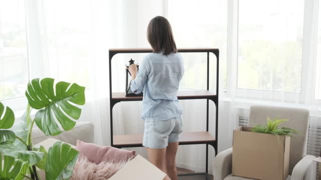 vídeos de stock e filmes b-roll de young woman moving into new apartment - arranjo