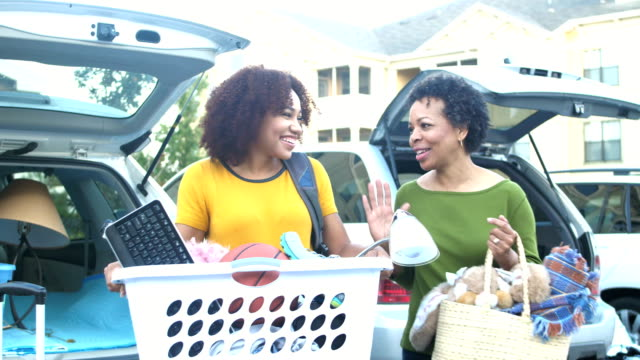 Young woman moving, talking with mother A young African-American woman happy to be moving. She is standing in a parking lot taking a laundry basket filled with personal belongings out of the car, talking with her mother. university stock videos & royalty-free footage