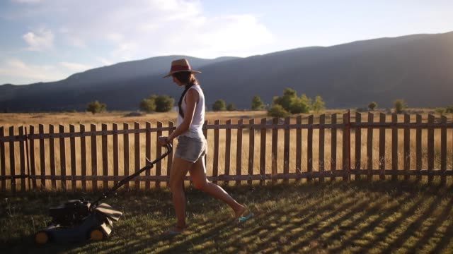 Young woman mowing the lawn outside her house
