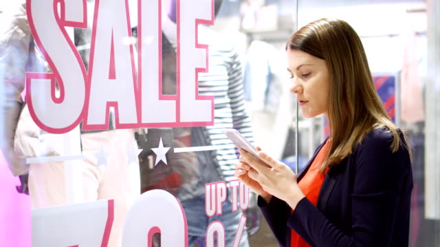 Young woman near window shop. Sale sign. Reading QR-codes by smartphone, checking prices online