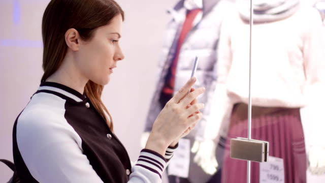 Young woman near window shop with mannequins. Reading QR-codes by smartphone, checking prices online Beautiful attractive young woman near window shop with mannequins. Reading QR-codes by smartphone, checking prices online. Shopping at the mall, sales time web browser stock videos & royalty-free footage