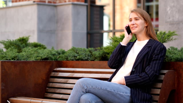 Young  Woman Negotiating on Phone, Discussing with Friend video