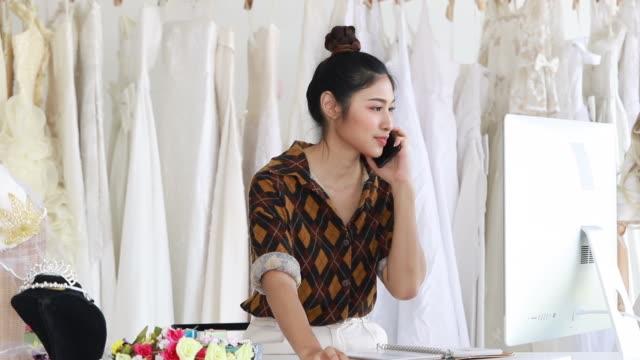 顧客に電話を話してブライダル店主の若い女性 - 美容院点の映像素材/bロール