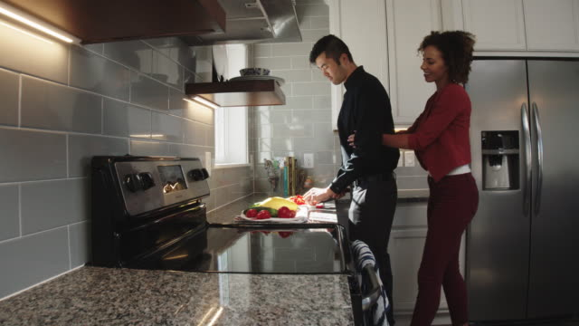 A Young Woman of Mixed Race Walks into a Kitchen and Hugs a Young Asian Man from Behind as He Slices Vegetables on the Counter of a Bright, Modern Kitchen