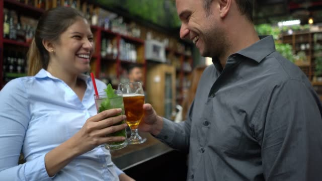 Young woman on a date with a handsome man enjoying beer and a mojito both flirting Young woman on a date with a handsome man enjoying beer and a mojito both flirting and looking very happy bar counter stock videos & royalty-free footage