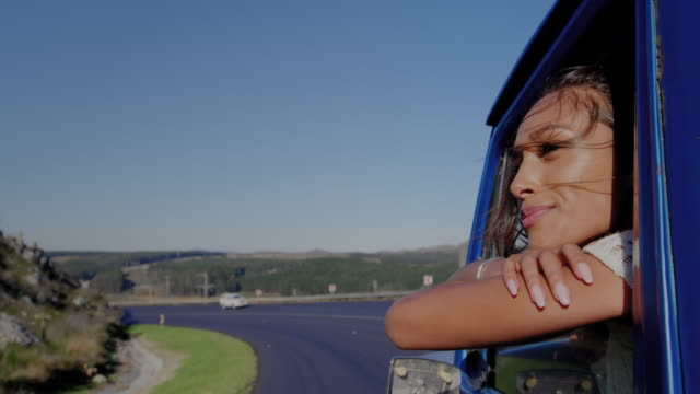 Young woman on a road trip in pick-up truck Side view of a young mixed race woman sitting in a pick-up truck, leaning out of a window during a road trip leaning stock videos & royalty-free footage