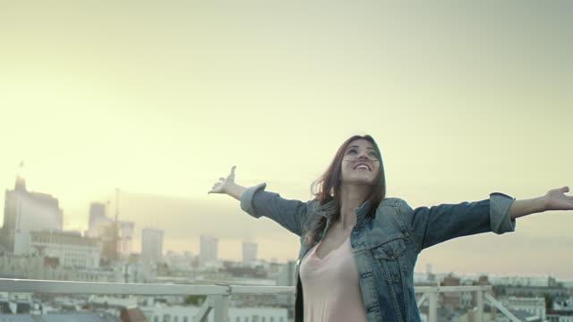옥상에 있는 젊은 여성. 자유를 누리다 - 환희 스톡 비디오 및 b-롤 화면