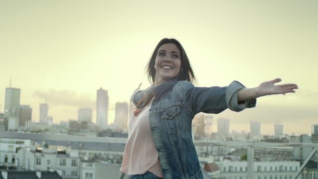 vídeos y material grabado en eventos de stock de una mujer joven en un tejado. disfrutar de la libertad - fuerza