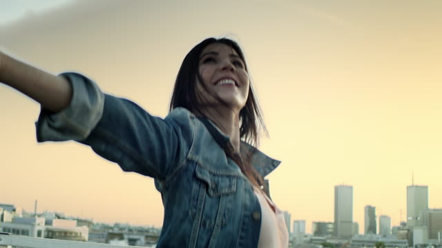 Young woman on a rooftop. Enjoying freedom video