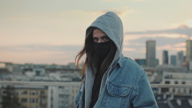 vídeos de stock e filmes b-roll de young woman on a rooftop. enjoying the sunset during pandemic - capuz