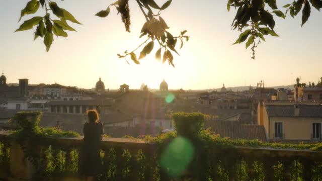 stockvideo's en b-roll-footage met jonge vrouw op balkon kijkt naar rome stadsgezicht - europe