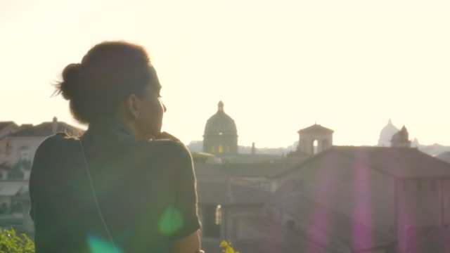 young woman on balcony looks at rome cityscape - объект мирового наследия юнеско стоковые видео и кадры b-roll