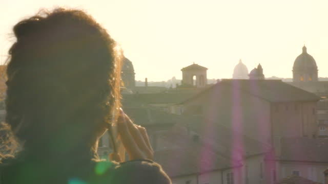 young woman on balcony talking on smartphone in front of rome cityscape - peter the apostle video stock e b–roll