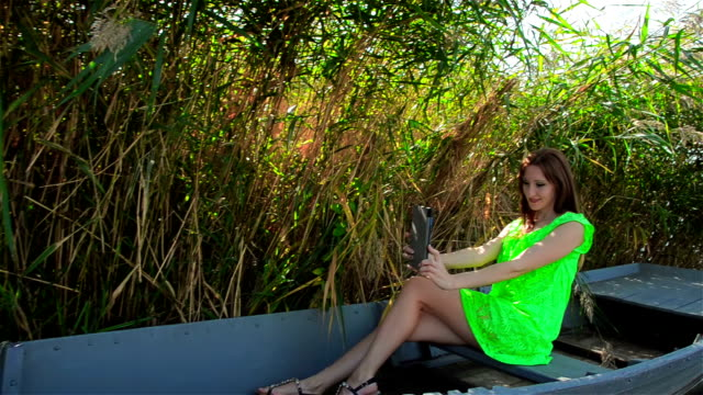 Young woman on boat doing selfie on tablet on wooden boat