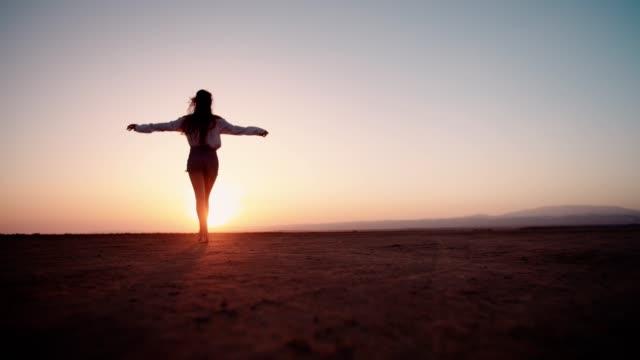 Jeune femme en vacances marchant pieds nus dans le désert au coucher du soleil - Vidéo