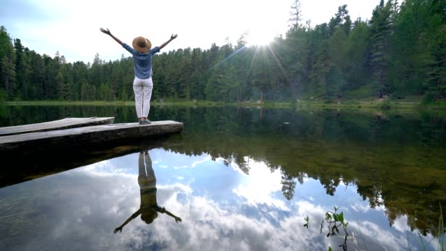 Young woman on lake pier stands arms outstretched, positive vibes video