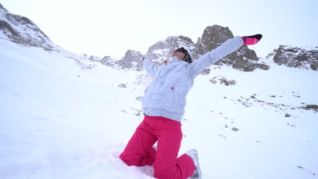 Young woman on ski slopes arms outstrtched video