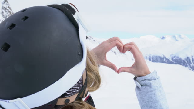 Young woman on ski slopes making heart shape video