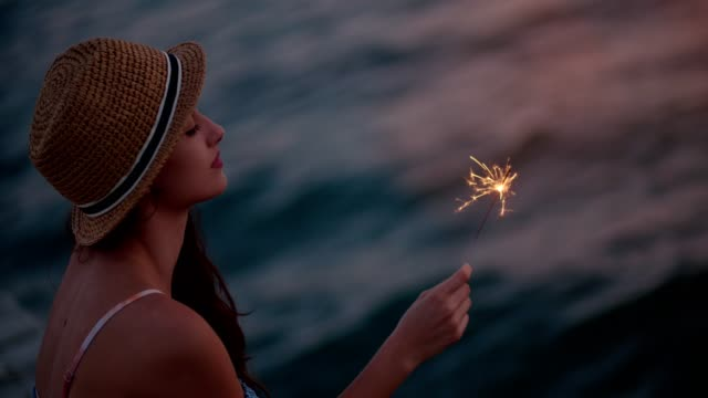 Young woman on summer holidays holding sparklers at the sea