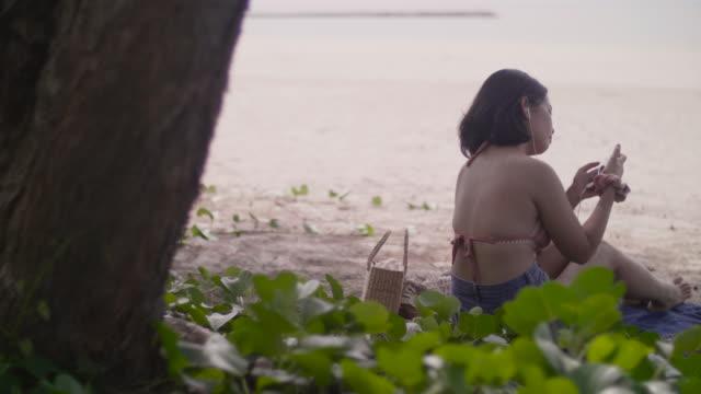 Young woman on the beach enjoying inserting earphones.