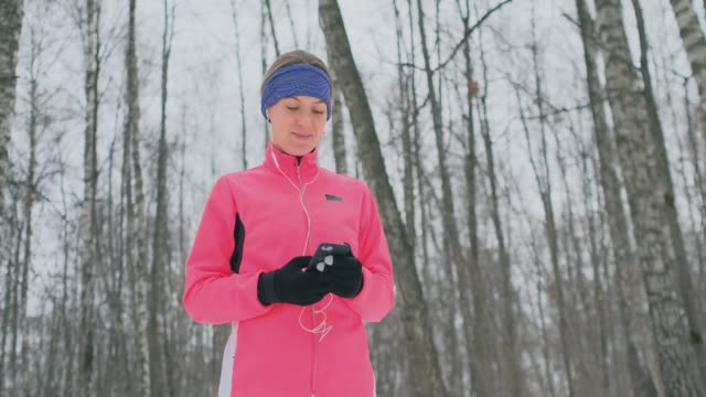 A young woman on the morning jog holds in her hands a smartphone picks a music track for training. Winter run. Use modern gadgets and training applications