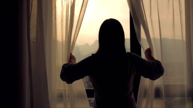 ung kvinna öppna gardin på morgonen - titta på utsikt bildbanksvideor och videomaterial från bakom kulisserna