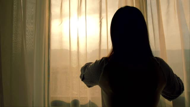 vídeos de stock e filmes b-roll de young woman open curtain in the morning - open window