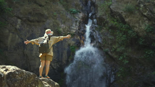 Young woman open her arms toward the waterfall in forest