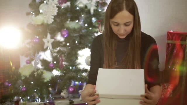 Jeune femme ouvrir un cadeau de Noël. - Vidéo
