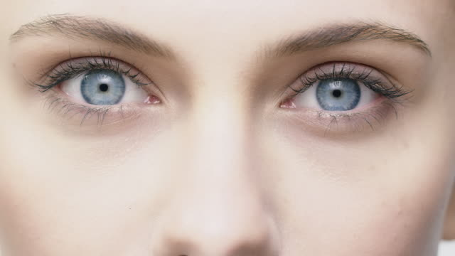Young woman opening and closing her blue eyes