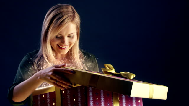 Young woman opening magical Christmas gift Family Christmas. Woman opening beautiful Christmas gift. Sparks, glitter and fireworks coming out of the box gifts stock videos & royalty-free footage