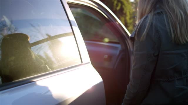 vídeos y material grabado en eventos de stock de mujer joven abriendo la puerta y entrar en el asiento del copiloto de un coche - manija