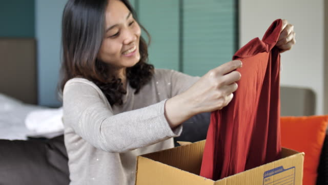 Young Woman Opens Cardboard Box at home video