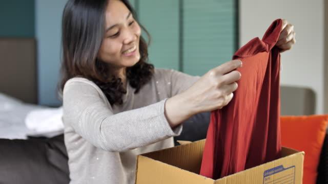 Junge Frau öffnet Karton zu Hause – Video
