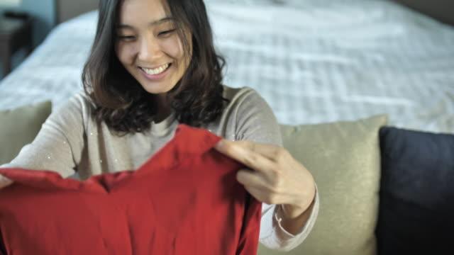 段ボール箱を開く若い女性が自宅の購入をお楽しみください。 - オンラインショッピング点の映像素材/bロール